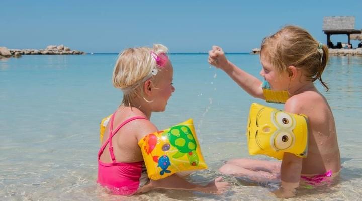 Kinderen spelen op het strand van LionsDive Resort