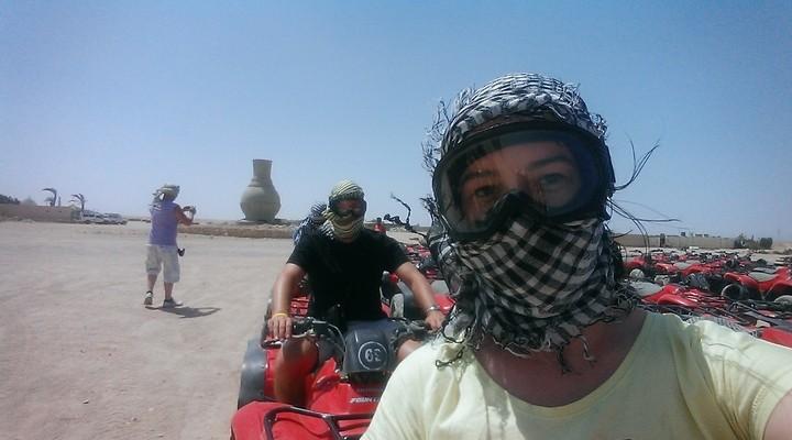 Met een sjaal omgebonden en een stevige bril op quad rijden in de woenstijn