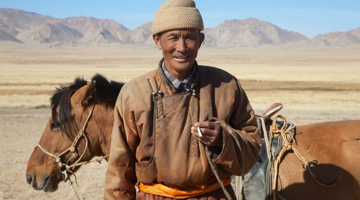 Nomade met paard in de steppen van Mongolie