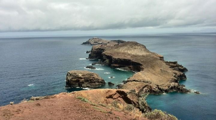 Een lange rots gelegen in de blauwe zee rondom Madeira