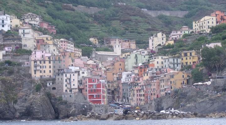 Riomaggiore met felgekleurde huizen en schilderachtige kliffen die in de diepblauwe zee storten