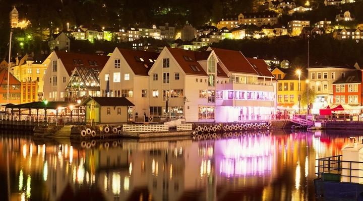Bergen in de avond met huizen aan het water