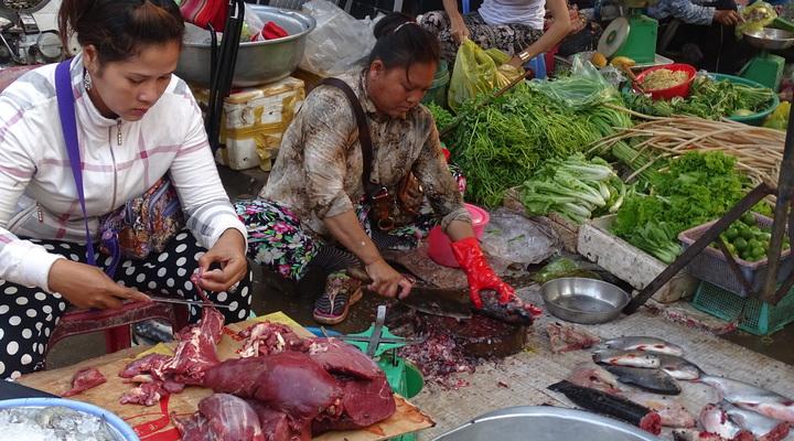 Vrouwen die eten aan het bereiden zijn op de Kratie Market